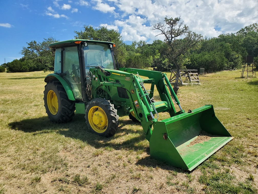 A Tractor In A Field Of Green Grass